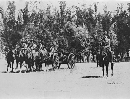 Troops on horseback, pulling a field gun.