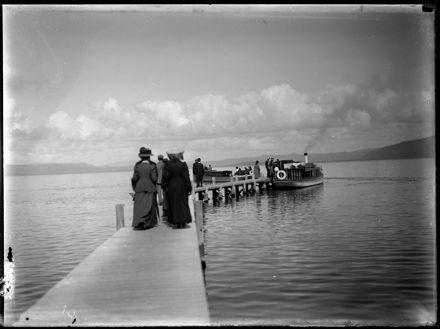Figures Walking Down Dock Towards Boat