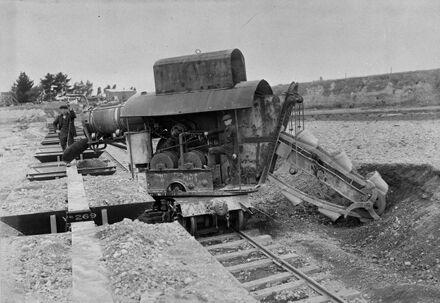 Men operating a metal loader at Longburn gravel pit.