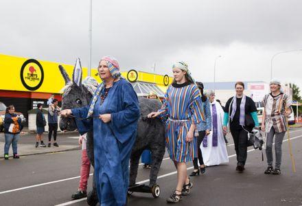 Mary, Joseph and a donkey on wheels walking past Tony's Tyre Service  at the Christmas Parade 2016
