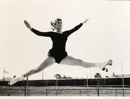 Deborah Rumsey executing split jump at Memorial Park roller skating rink, 1966