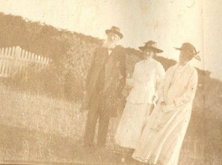 Old man and two women by picket fence