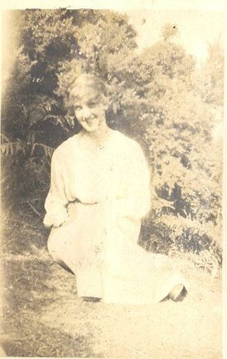 Young woman sitting on lawn.