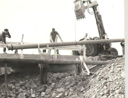 Replacing pipes alongside bridge