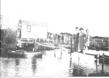 Cottage & people beside Hokio Stream