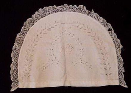Teapot cosy cover with embroidered arching sprigs.