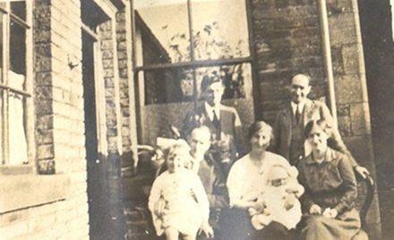 Family group sitting outside brick house